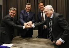 Министр энергетики и угольной промышленности Украины Эдуард Ставицкий, президент Виктор Янукович, нидерладнский премьер Марк Рютте и глава Royal Dutch Shell Питер Возер жмут друг другу руки на церемонии подписания соглашения в Давосе 24 января 2013 года. Украина подписала с компанией Shell первое в СНГ соглашение о разделе продукции от добычи сланцевого газа, реализация которого поможет снизить зависимость Киева от импорта дорожающего российского газа, говорится в совместном пресс-релизе. REUTERS/Pascal Lauener