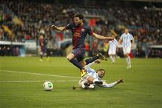 Le milieu de terrain du FC Barcelone Cesc Fabregas esquive un tacle du défenseur de Malaga Martin Demichelis, jeudi soir à Malaga. Le Barça, tenant du titre, affrontera son ennemi juré du Real Madrid en demi-finale de la Coupe du Roi, le club catalan ayant éliminé son adversaire andalou (4-2 jeudi soir, au retour et 6-4 sur les deux matches). /Photo prise le 24 janvier 2013/REUTERS/Jon Nazca