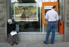 Женщина просит милостыню в Тбилиси у банкомата, в котором мужчина снимает деньги 20 июня 2012 года. Международный валютный фонд связал рост экономики Грузии с политической стабильностью в стране, пережившей смену власти в прошлом году, и восстановлением экономических связей с соседней Россией. REUTERS/David Mdzinarishvili