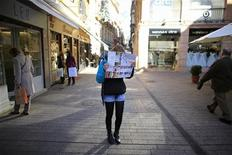 A woman covers her face with a city map in reaction to the photographer, in the central Andalusian capital of Seville January 3, 2013. REUTERS/Marcelo del Pozo