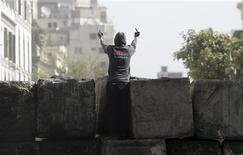 Varias ciudades de Egipto fueron escenario el viernes de enfrentamientos con la policía en el segundo aniversario del levantamiento que derrocó a Hosni Mubarak por las protestas contra el presidente electo islamista, al que acusan de traicionar la revolución. En la imagen del 25 de enero se puede ver a un manifestante haciendo un gesto a los antidisturbios en una calle cerca de la plaza Tahrir de El Cairo. REUTERS/Amr Abdallah Dalsh