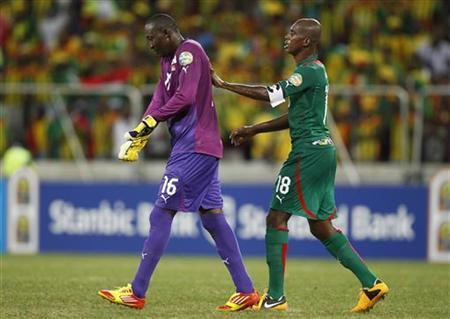 Burkina Faso's goalkeeper Abdoulaye Soulama (L) is escorted by his teammate Charles Kabore after Soulama was shown a red card during their African Nations Cup (AFCON 2013) Group C soccer match against Ethiopia in Nelspruit, January 25, 2013. REUTERS/Thomas Mukoya