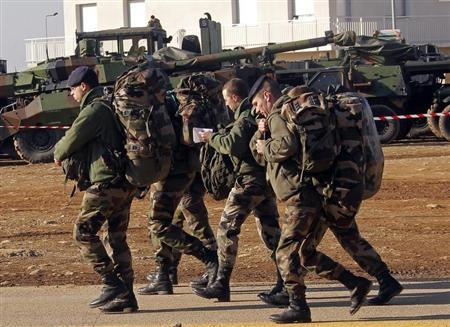 French soldiers, who prepare for their departure for Mali, walk past armoured vehicles with theirs belongings during a visit of the French Defence Minister at the military base of Miramas, southern France, January 25, 2013. REUTERS/Jean-Paul Pelissier