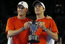 Bob and Mike (L) Bryan of the U.S. pose with the trophy after defeating Robin Haase Igor Sijsling of Netherlands in their men's doubles final match at the Australian Open tennis tournament in Melbourne, January 26, 2013. REUTERS/Damir Sagolj