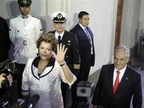 Presidente Dilma Rousseff (E) acena para a mídia, ao lado do presidente do Chile Sebastián Piñera após chegar ao palácio La Moneda em Santiago. 26/01/2013 REUTERS/Andres Stapff