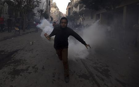 A protester opposing Egyptian President Mohamed Mursi throws a tear gas canister, which was earlier thrown by riot police, during clashes along Mohamed Mahmoud street which leads to the Interior Ministry, near Tahrir Square in Cairo January 26, 2013. REUTERS/Amr Abdallah Dalsh