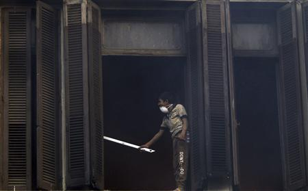 A youth protester opposing Egyptian President Mohamed Mursi damages the windows of a school during clashes with riot police along Mohamed Mahmoud street which leads to the Interior Ministry, near Tahrir Square in Cairo January 26, 2013. REUTERS/Amr Abdallah Dalsh