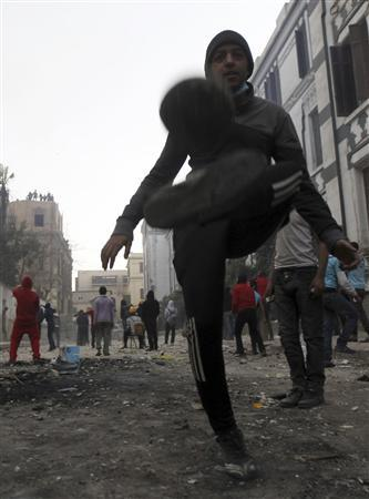 A protester opposing Egyptian President Mohamed Mursi plays with a soccer ball as other protesters throw stones towards riot police during clashes along Mohamed Mahmoud street which leads to the Interior Ministry, near Tahrir Square in Cairo January 26, 2013. REUTERS/Amr Abdallah Dalsh