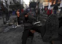 La policía lanzó gases lacrimógenos a decenas de manifestantes armados con piedras el domingo en El Cairo, en el cuarto día de violencia callejera que se ha cobrado la vida de al menos 41 personas e intensificado los retos que afronta el presidente Mohamed Mursi. En la imagen, un manifestante durante una protesta contra Mursi cerca de la plza Tahrir, en El Cairo, el 26 de enero de 2013. REUTERS/Amr Abdallah Dalsh