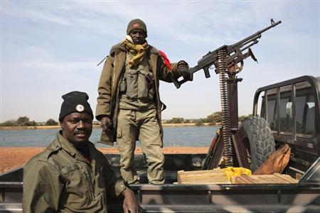 Malian soldiers stand guard in a Malian army pickup truck mounted with a machine gun in Diabaly January 26, 2013. REUTERS/Joe Penney