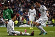 Cristiano Ronaldo logró un hat-trick y superó los 300 goles en su carrera en clubes, que dejó atrás una turbulenta semana el domingo con una victoria en casa por 4-0 contra el Getafe en Liga y reduciendo provisionalmente su diferencia con el Atlético de Madrid y el Barcelona. En la imagen, Ronaldo y Özil celebran un gol en el partido contra el Getafe. REUTERS/Juan Medina