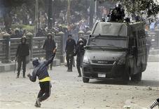Un manifestant lance des pierres contre un véhicule de la police non loin de la place Tahrir au Caire. Plusieurs dizaines de manifestants ont continué dimanche à affronter la police au Caire lors d'une quatrième journée consécutive de violences en Egypte, où l'opposition essaie de défier dans la rue le président islamiste Mohamed Morsi. /Photo prise le 27 janvier 2013/REUTERS/Mohamed Abd El Ghany