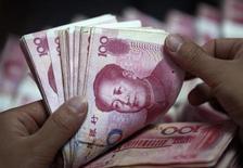 """Um funcionário de banco conta notas de iuan em Hauaibei, na província de Anhui, China. A moeda chinesa está sendo negociada em um nível """"relativamente próximo"""" do equilíbrio frente ao dólar norte-americano, disse uma autoridade sênior do banco central do país à agência de notícias estatal Xinhua, citando a desaceleração no crescimento das imensas reservas estrangeiras da China como evidência de que o iuan está aproximando-se da harmonia. 8/06/2012 REUTERS/Stringer"""