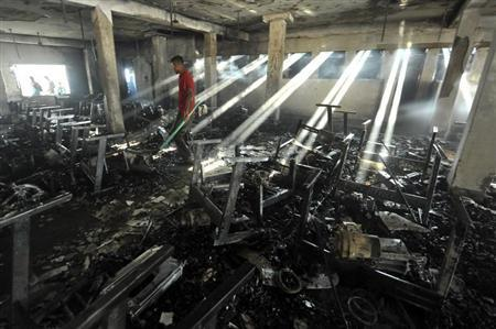 People look for things to salvage after a fire at the Smart Fashions garment factory in Dhaka January 26, 2013. REUTERS/Stringer