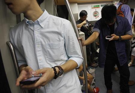 1月28日、米アップルの成長の原動力となってきた「iPhone」だが、シンガポールや香港などアジアの裕福な消費者の間では人気に陰りも出始めている。シンガポールの電車の中で26日撮影(2013年 ロイター/Edgar Su)