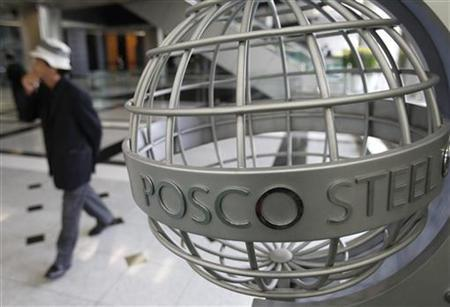 A man walks past a logo of steelmaker POSCO at the company's headquarters in Seoul October 25, 2010. REUTERS/Truth Leem/Files