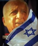 """Siete años después de sufrir un masivo ataque cerebral que lo sumió en un coma, el ex primer ministro israelí Ariel Sharon ha sorprendido a sus médicos mostrando """"un cierto grado de consciencia"""", dijo el domingo un experto que lo examinó utilizando un escáner. En la imagen, una bandera israelí junto a un retrato de Sharon en una fotografía de archivo de 2006 en Newe Ilan, a unos 15 km de Jerusalén. REUTERS/Goran Tomasevic"""