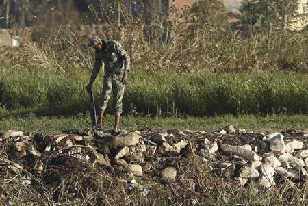A member of Egyptian army washes his leg outside a tent at the Nile river into the Qursaya Island in Cairo January 19, 2013. REUTERS/Amr Abdallah Dalsh