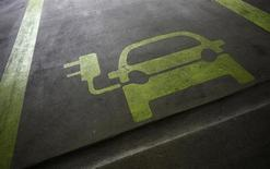 Нарисованный на асфальте автомобиль, обозначающий место для парковки электромобилей в Гонконге, 29 января 2012 года. Три мировых автопроизводителя решили объединить усилия для совместной разработки автомобилей, работающих от топливных элементов, которые поступят продажу в 2017 году. REUTERS/Tyrone Siu