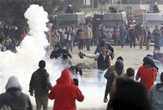 Manifestantes contrários ao presidente Mohamed Mursi fogem de gás lacrimogêneo disparado pela polícia de choque durante confrontos perto da Praça Tahrir, no Cairo. Mursi decretou estado de emergência durante um mês em três cidades do canal de Suez, onde dezenas de pessoas foram mortas em protestos que varreram o país e agravaram a crise política que acua o líder islâmico. 27/01/2013 REUTERS/Amr Abdallah Dalsh
