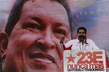 Venezuela's Vice President Nicolas Maduro talks in front of a screen with an image of Venezuela's President Hugo Chavez during a rally to commemorate the 55th anniversary of the collapse of the last Venezuelan dictatorship in Caracas January 23, 2013. REUTERS/Jorge Silva