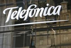 """Telefónica ha seguido los pasos de la eléctrica italiana Enel al pedir a los bancos que prorroguen una parte de sus créditos actuales dentro de un crédito """"forward start"""", dijeron el lunes fuentes bancarias a RPLC, un servicio de Thomson Reuters especializado en deuda corporativa. En la imagen de archivo, varias figuras reflejadas en el logo del gigante de las telecomunicaciones Telefónica en Madrid, el 3 de diciembre de 2012. REUTERS/Andrea Comas"""