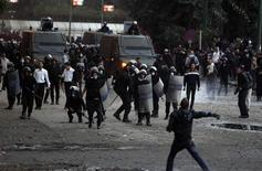 Un hombre murió tiroteado el lunes en el quinto día de una ola de violencia en Egipto que ha dejado un saldo de 50 muertos y llevó al presidente islamista a declarar el estado de emergencia en un intento por poner fin a la agitación que sacude al mayor país del mundo árabe. En la imagen, un manifestante contrario al presidente de Egipto Mohamed Mursi lanza una piedra a policías antidisturbios en enfrentamientos en el puente Qasr Al Nil, que lleva a la plaza Tahrir, en El Cairo, el 28 de enero de 2013. REUTERS/Mohamed Abd El Ghany