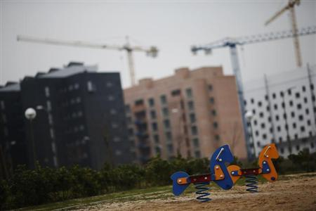 A children's playground is pictured near blocks of houses under construction on the outskirts of Madrid December 7, 2012. REUTERS/Susana Vera