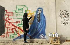 An Afghan artist Malina Suliman paints graffiti on a wall in Kandahar city December 30, 2012. Charred bodies lay scattered against blood-stained walls in a recent installation by Afghan artist Malina Suliman. For Afghanistan, the only thing out of place in this gruesome scene is that the blood is not real, but is red paint. Picture taken on December 30, 2012. REUTERS/ Ahmad Nadeem