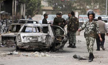 Members of the Egyptian Army keep guard near burnt vehicles in front of a police station, which was stormed into and set on fire by protesters, in the city of Suez January 28, 2013. REUTERS/Stringer (EGYPT - Tags: POLITICS CIVIL UNREST MILITARY)