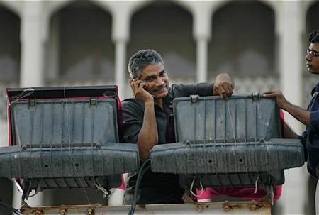 An electrician speaks on his mobile phone in Mumbai October 11, 2006. REUTERS/Sima Dubey/Files