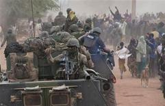 French troops aboard armoured vehicles are greeted by the population as they arrive in Timbuktu in this January 28, 2013 picture provided by the French Military audiovisual service (ECPAD) January 29, 2013. REUTERS/Arnaud Roine/ECPAD/Handout