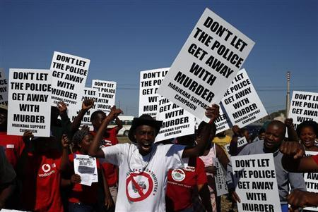 Demonstrators wave placards during a site inspection by the judicial commission of inquiry into the shootings at Lonmin's Marikana mine in this file photo taken October 1, 2012. REUTERS/Mike Hutchings