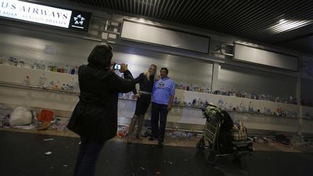 Tourists pose for a picture in front of accumulated garbage during a strike by airport cleaners at Madrid's Barajas international airport January 29, 2013. REUTERS/Sergio Perez