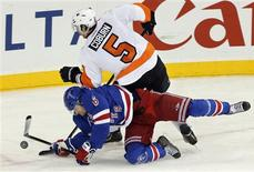 New York Rangers defenseman Anton Stralman (6) dives to stop a shot by Philadelphia Flyers defenseman Braydon Coburn (5) in the third period of their NHL hockey game at Madison Square Garden in New York, January 29, 2013. REUTERS/Ray Stubblebine