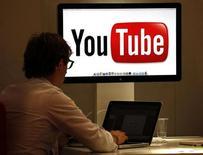 Посетитель на стенде YouTube на выставке MIPCOM в Каннах 3 октября 2011 года. Принадлежащий Google Inc видеохостинг YouTube планирует открыть платные подписки для части контента на своем вебсайте в конце этого года, сообщил ресурс AdAge со ссылкой на неназванные источники. REUTERS/Eric Gaillard