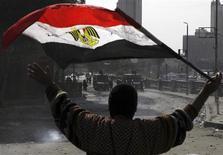 Manifestante contrário ao presidente egípcio Mohamed Mursi segura bandeira nacional durante confronto com a polícia de choque na ponte de Qasr Al Nil, no Cairo. Mursi chegou na quarta-feira à Alemanha na tentativa de convencer a Europa das suas credenciais democráticas, num momento em que uma onda de violência em seu país já deixou mais de 50 mortos. 28/01/2013 REUTERS/Amr Abdallah Dalsh