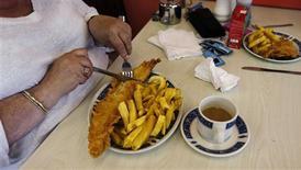 ¿Quiere perder peso? Comer antes podría ayudarle. En la imagen, de archivo, una mujer come un plato de pescado y patatas fritas en Londres. REUTERS/Eddie Keogh