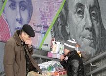 Прохожий и уличная торговка стоят возле рекламного плаката с изображенем украинской гривны и американского доллара в Киеве 19 ноября 2012 года. Рост валового внутреннего продукта Украины в 2012 году замедлился до 0,2 процента с 5,2 процента в 2011 году, сообщило предварительную оценку министерство экономического развития и торговли. REUTERS/Anatolii Stepanov