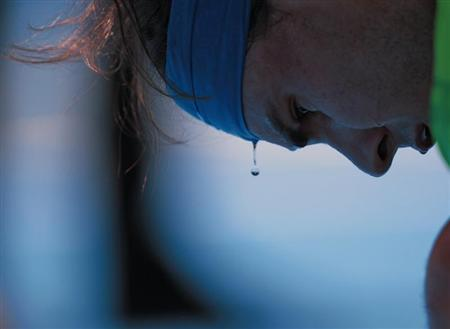 A bead of sweat drips from Rafael Nadal of Spain's head during a break in between games against Feliciano Lopez of Spain at the Australian Open tennis tournament in Melbourne January 22, 2012. REUTERS/Vivek Prakash
