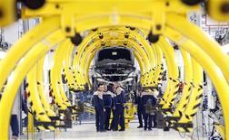 Un grupo de empleados frente a un nuevo vehículo Maserati en una planta de la firma en Turín,Italia, ene 30 2013. La confianza económica de la zona euro mejoró más de lo previsto en todos los sectores en enero, al registrar su tercer aumento consecutivo, en una señal de que la economía podría estar emergiendo desde un punto bajo en el cuarto trimestre del 2012. REUTERS/Stefano Rellandini