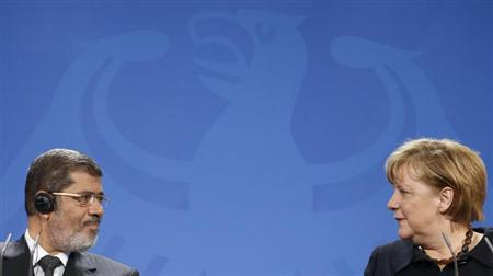 German Chancellor Angela Merkel (R) and Egyptian President Mohamed Mursi address a news conference at the Chancellery in Berlin January 30, 2013. REUTERS/Fabrizio Bensch (GERMANY - Tags: POLITICS)