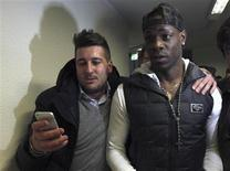 A fan flanks soccer player Mario Balotelli of Italy as Balotelli arrives at the AC Milan medical centre in Busto Arsizio near Milan January 30, 2013. Balotelli, the hot-tempered forward who had been playing for Manchester City, is poised to sign for AC Milan, the club owned by the former prime minister vying for a political comeback. REUTERS/Stringer