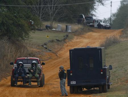 Law enforcement officials in bomb squad protective gear are driven to the scene of a shooting and the bunker as the standoff with the shooter continues in Midland City, Alabama January 30, 2013. REUTERS/Phil Sears (UNITED STATES - Tags: CRIME LAW)