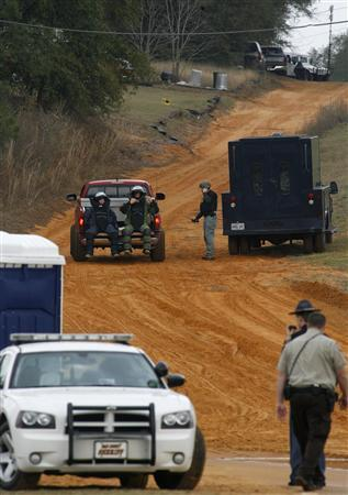 Law enforcement officials in bomb squad protective gear are driven to the scene of a shooting and the bunker as the standoff with the shooter continues in Midland City, Alabama January 30, 2013. A standoff continued on Wednesday with a gunman who boarded an Alabama school bus and fatally shot the driver before fleeing with a young child and holing up in an underground bunker, authorities said. REUTERS/Phil Sears (UNITED STATES - Tags: CRIME LAW)