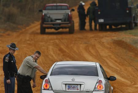 As bomb squad personnel (in back) prepare to enter the scene, law enforcement officials turn back a vehicle at a roadblock near a standoff with the shooter in Midland City, Alabama January 30, 2013. REUTERS/Phil Sears