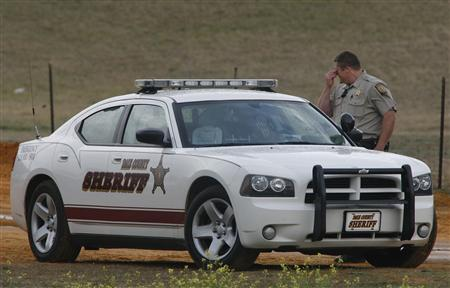 A Dale County Sheriff's deputy reacts as he stands at a roadblock near the scene of a shooting and the standoff with the shooter in Midland City, Alabama January 30, 2013. REUTERS/Phil Sears