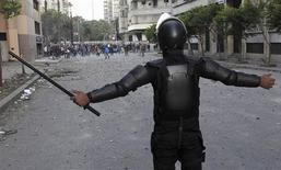 A riot police officer stands in front of anti-Mursi protesters during clashes in Simon Bolivar Square, which leads to Tahrir Square, in Cairo, January 30, 2013. REUTERS/Mohamed Abd El Ghany (EGYPT - Tags: CRIME LAW CIVIL UNREST POLITICS)