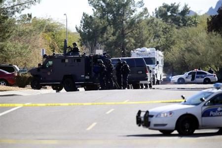 A SWAT team stands in position outside of a home of a suspected gunman who fired shots inside an office building during business hours in Phoenix, Arizona January 30, 2013. At least three people were shot on Wednesday at a business complex in Phoenix, and one was in an extremely critical condition, police said. REUTERS/Joshua Lott