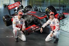 McLaren presentó el jueves su monoplaza para 2013 con un recuerdo al pasado, en una temporada en la que celebra 50 años disputando grandes premios y en la que tiene ganas de volver a lo más alto de la Fórmula Uno. En la imagen, los pilotos de McLaren Jenson Button y Sergio Pérez, en la sede de la compañía en Woking, en el sur de Inglaterra, el 31 de enero de 2013. REUTERS/Stefan Wermuth